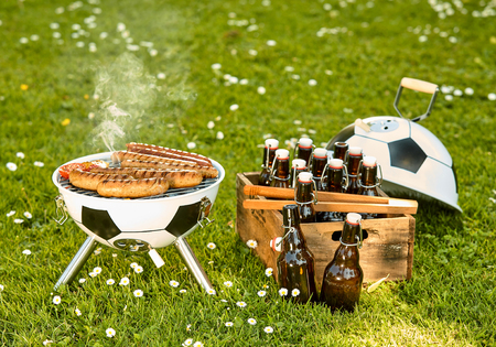 Soccer themed barbecue with meat grilling on a ball shaped BBQ and box of bottled craft beers in a green spring meadow