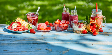 Summer food and drink strawberries in the garden. Ice cream,waffles, smoothies, bowl and punch, desserts in the garden for coffee time. Stockfoto - 102243802
