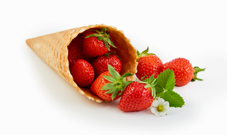 Cornet wafer ice cream cone with fresh ripe red strawberries spilling out onto a white background Stock Photo