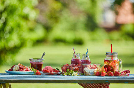 Fresh, healthy, vibrant summer berry smoothie bowl, juices and desserts picnic on a bright outdoor table setting. Stock Photo