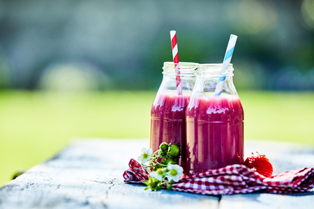 Bright, vibrant strawberry smoothies in glass jars on an outdoor summer picnic table setting.