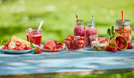 Fresh, sweet, healthy summer berry menus, smoothie bowls and juices on a bright outdoor table setting in a panoramic aspect ratio.
