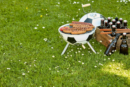 Celebration barbecue for the  with sausages grilling over a ball shaped portable BBQ with a crate full of bottled beer alongside in a meadow