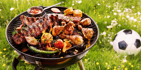 Summer or spring barbecue outdoors in a meadow with dandelions and a soccer ball with assorted vegetables, spicy spare ribs and chicken legs grilling on the fire Stockfoto