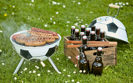 Bratwurst sizzling on the grill at a Soccer themed BBQ with ball shaped barbecue and crate full of bottles of craft beer in a green field