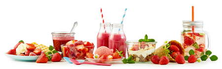 Strawberry themed panorama food still life with assorted recipes including waffle and cream, ice cream, fruit salad, muesli and yogurt, whole ripe berries and infused water over white Foto de archivo - 102243812