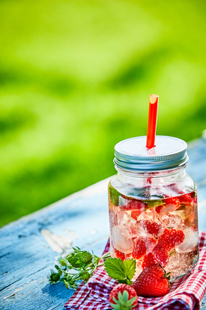 Fresh, chilled fruit and berry infused punch bowl in a glass jar with a straw on a bright outdoor table setting.