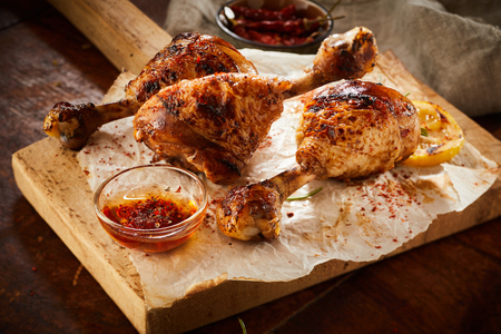Spicy seasoned chicken legs or drumsticks grilled over a summer barbecue and served on paper on a rustic wooden board