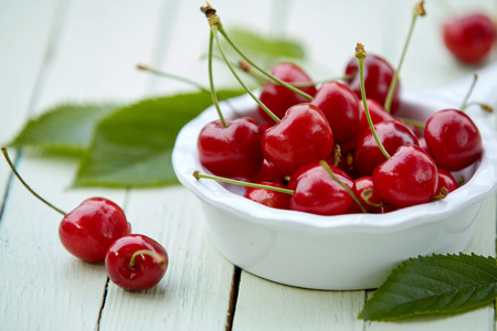 Close up view of a bowl of delicious ripe red cherries on a white wooden garden table in summer