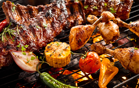 Portions of spicy spare ribs and chicken legs grilling over a hot fire on a BBQ with assorted fresh summer vegetables