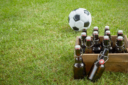 Celebrating the World Cup with friends with a wooden crate of bottled craft beers and a soccer ball on green grass with copy space ready for a party Imagens