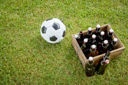 High-angle view of a rustic wooden case full of cold bottles of beer next to a soccer ball on green grass in a sunny day