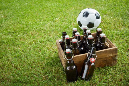 Old wooden crate of bottled craft beer with a soccer ball on fresh green grass with copy space conceptual of the World Cup