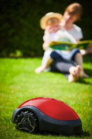 Close-up of a modern autonomous mower on green grass in front of a young mother and her child in a sunny day