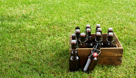 Old wooden crate filled with bottles of craft beer on green grass with copy space