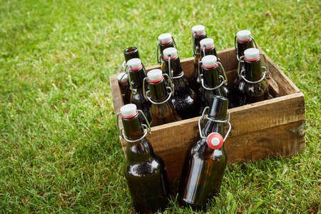 Wooden crate with unlabelled bottles of beer or lager at a tilted angle outdoors on green grass with copy space for a summer picnic