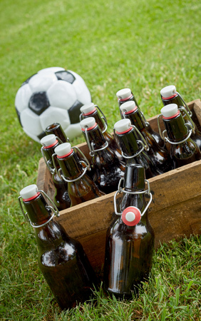 Bottled beer in an old wooden crate with a championship soccer ball on green grass ready for a party celebration and get together for the World Cup in a tilted angle close up view