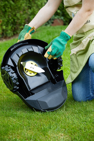 Woman working with an autonomous lawn mower on a green spring lawn showing the underside of the machine