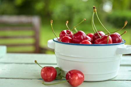 Close up view of red fresh juicy cherries in bowl on wooden garden table Stock Photo