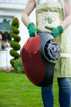 Woman wearing green gardening gloves while holding an autonomous rechargeable mower