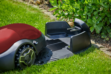 Close-up of a red autonomous mower moving towards the charging station in the garden