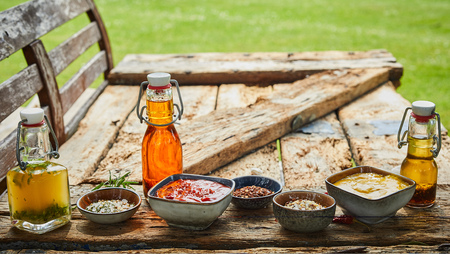 Selection of condiments and spices on a rustic weathered wooden garden table with aromatic oils, ketchup, mustard and spice rubs ready for a BBQ