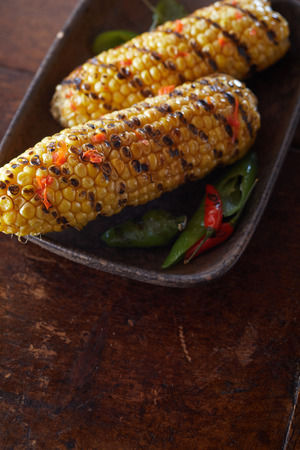 Fresh prepared marinated chili BBQ corn from summer grill served in a brown bowl on a rustic plate and table.