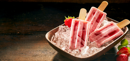 Refreshing frozen fresh strawberry ice cream displayed in a bowl of ice over a rustic wooden counter with dark background and copy space in panorama banner format