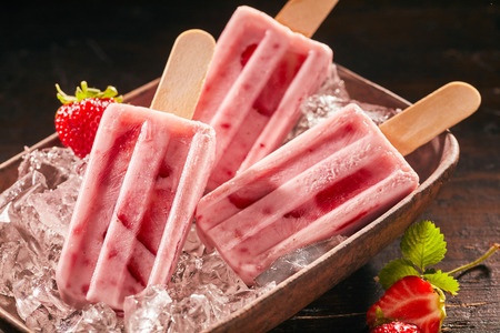 Three delicious summer snacks. Delicious frozen ice cream or ice lollies with strawberry and yoghurt on rustic plate.
