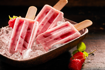 Tasty ice lolly with strawberries on a plate filled with crushed ice. Stock Photo - 103462618