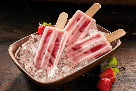 Dish of healthy fresh strawberry ice cream or frozen suckers on ice with scattered berries on a rustic wooden table for a refreshing summer treat 스톡 콘텐츠