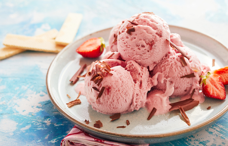 Sundae with three scoops of craft ice cream flavored with fresh strawberries and garnished with chocolate shavings served on a pottery plate Zdjęcie Seryjne - 103462626