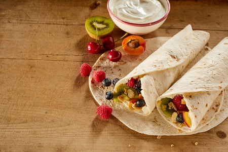 Assorted fresh tropical fruit in a wrap or pancake with whipped cream including kiwi, raspberry, blueberry, apple, apricot and cherries viewed high angle on a wooden table with copy space