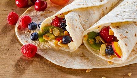 Two tasty healthy summer fruit wraps with roasted mixed nuts and whipped cream on a wooden table with scattered fresh tropical fruit ingredients