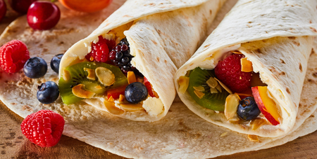 Close up of fresh tropical fruit wraps filled with whipped cream, mango, blueberries, apple, raspberries, kiwi, cherries and chopped roasted nuts