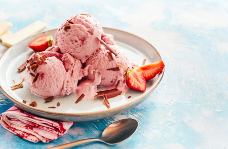 Tasty strawberry ice-cream sundae in a parlour topped with flakes of chocolate and fresh berries over a mottled blue background with copy space