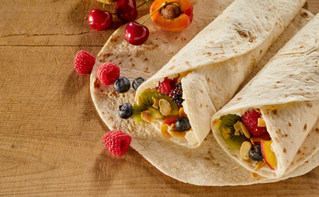 Tasty wraps filled with assorted fresh tropical fruit, cream and nuts on a wooden table with ingredients and copy space