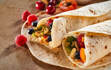 Close up on two healthy fresh fruit and nut wraps with assorted tropical summer fruit and whipped cream on a wooden table with scattered ingredients