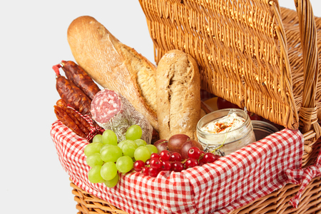 Grapes, red currants, salami, herb spread and bread for a summer picnic packed in a wicker basket in a close up cropped view on a white background