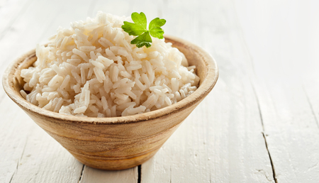 Rustic bowl of cooked long grain rice ready to serve as an accompaniment to a meal garnished with parsley Stock Photo - 104039921