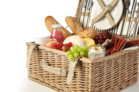 Vintage wicker picnic hamper filled with food including fresh fruit, assorted cheeses, spicy sausages, baguette and juice isolated on white in a cropped view