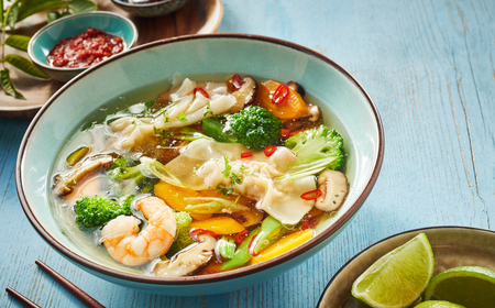 Wonton soup with dumplings, fresh vegetables and shrimp seasoned with spicy chili and served in a bowl with chopsticks and lime