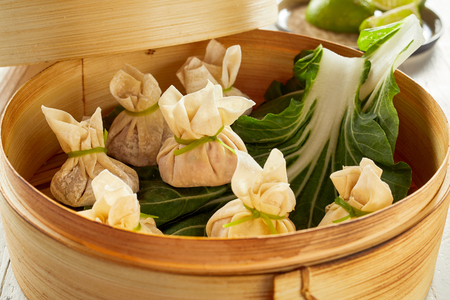 Taditional Asian dim sum dumplings on green cabbage leaves in bamboo basket