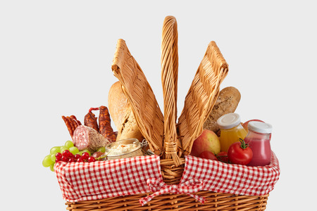 Picnic hamper filled with healthy fresh food including fruit, juice, salami, crusty bread, spread and tomatoes isolated on white