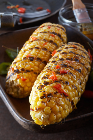 Macro or close up of barbecued corn on rustic dark background Stockfoto