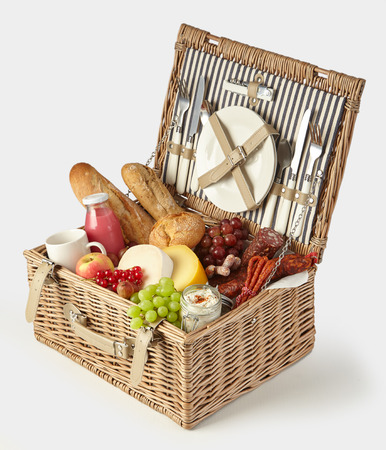 Old vintage style picnic hamper packed with food for a healthy summer lunch outdoors with fresh fruit and juice, cheeses, spicy sausages, spread and baguettes isolated on white
