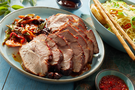 Plate of delicious succulent carved sliced Chinese char siu or spicy marinated grilled or barbecued pork in a close up view Stock Photo - 104039855