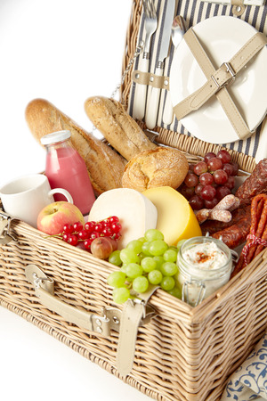 Healthy fresh fruit, spicy sausages bread and cheese in a hamper with a bottle of juice or smoothie ready for a summer picnic