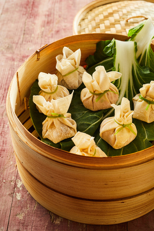Traditional Asian fresh dim sum dumplings arranged on green cabbage leaves in bamboo basket Stock Photo - 104039858