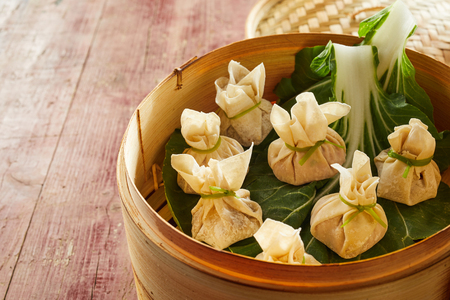 Traditional Asian fresh dim sum dumplings served on green cabbage leaves in bamboo basket